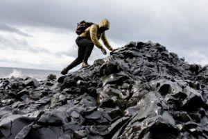 black man climbs pile of refuse on a beach
