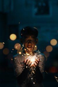 Asian teen holds sparkler in hand stem education