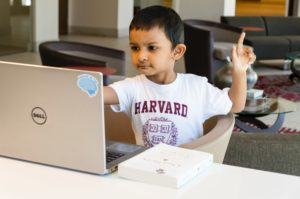 Young boy of color wearing a Harvard University shirt at a laptop looking determined to learn problem-slving